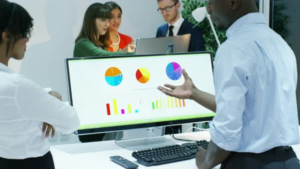 Business group in modern office, looking at charts and graphs on computer screen. Royalty-free stock video