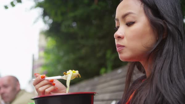 Portrait of beautiful young woman eating lunch outdoors in the city. Royalty-free stock video