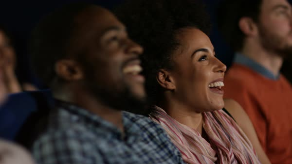 Couple watching a film with in crowded movie theatre, laughing at the action on screen. Royalty-free stock video