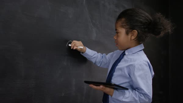 Cute little boy with tablet computer writing math sum on blackboard. Royalty-free stock video