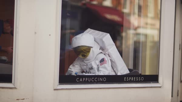 Astronaut with cup of coffee, sitting by the window in coffee shop. Royalty-free stock video