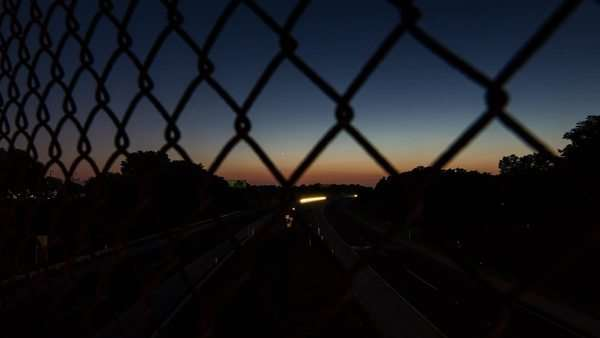 Timelapse of Cars driving down a large high way, shot through a chain linked fence. Royalty-free stock video