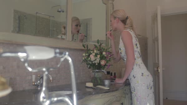 Medium wide shot of woman applying makeup in the bathroom Royalty-free stock video