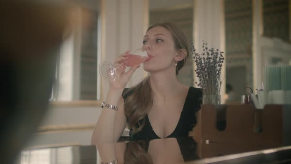 Medium shot of young woman drinking champagne in the lobby Royalty-free stock video