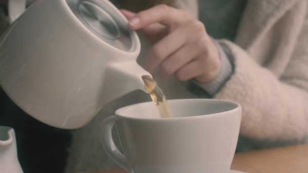 Hand-held shot of a woman pouring tea into a mug Royalty-free stock video