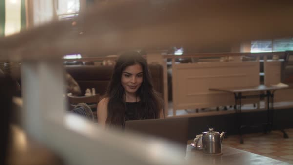 Hand-held shot of a woman looking at her laptop in a cafe Royalty-free stock video