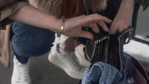 Hand-held shot of a woman searching through her handbag Royalty-free stock video