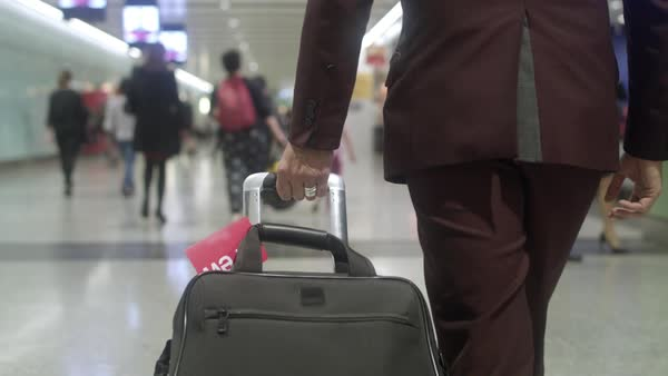 Hand-held shot of a man pulling his luggage Royalty-free stock video