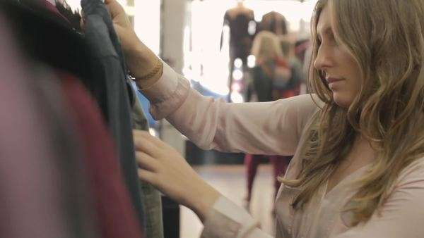 Medium shot of a woman browsing clothes in a boutique Royalty-free stock video