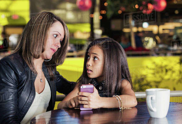 Young mother and her daughter in a cafe looking at a smart phone while taking a break from shopping and being concerned about content being viewed; St. Albert, Alberta, Canada Royalty-free stock photo