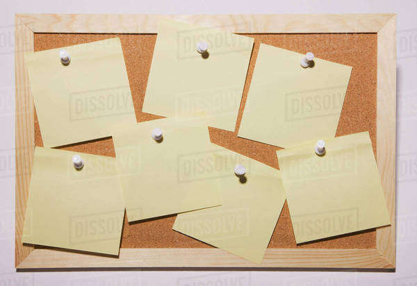 Yellow notes pinned to a cork board Royalty-free stock photo