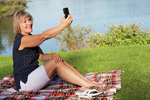 Mature woman taking her picture with a cell phone while relaxing in Hawrelak Park; Edmonton, Alberta, Canada Royalty-free stock photo