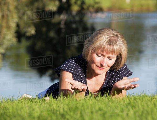 A woman on the grass in a park in prayer; Edmonton, Alberta, Canada Royalty-free stock photo