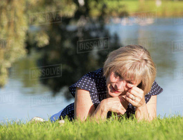 A woman on the grass in a park crying; Edmonton, Alberta, Canada Royalty-free stock photo