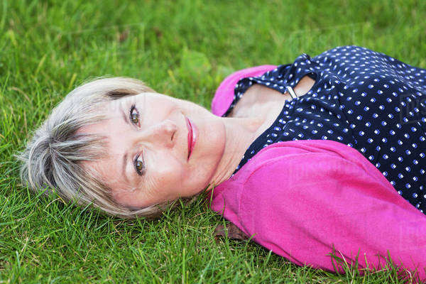 Portrait of a woman laying on the grass in a park; Edmonton, Alberta, Canada Royalty-free stock photo