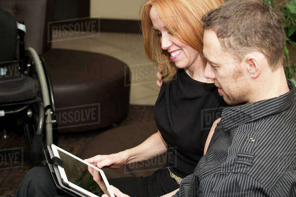 Couple looking a tablet together, wife with a disability; Edmonton, Alberta, Canada Royalty-free stock photo