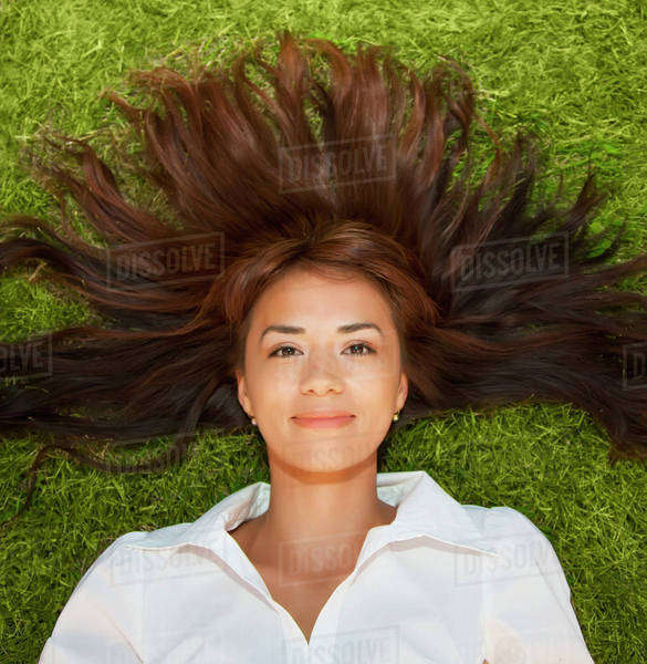 Portrait of a young woman laying on the grass with her long hair fanned out around her; Edmonton, Alberta, Canada Royalty-free stock photo