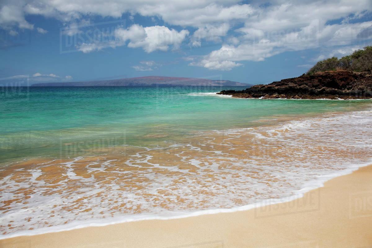Hawaii, Maui, Makena, Rocky shore of Makena beach, land in distance  stock  photo