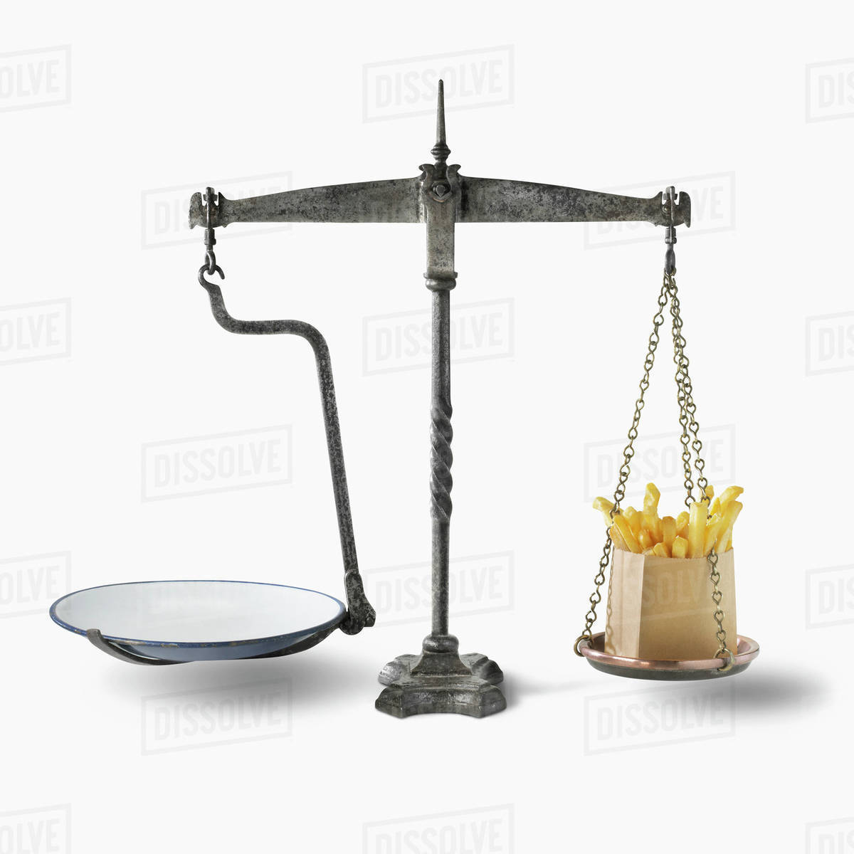 A weigh scale with french fries on one side of the scale stock photo