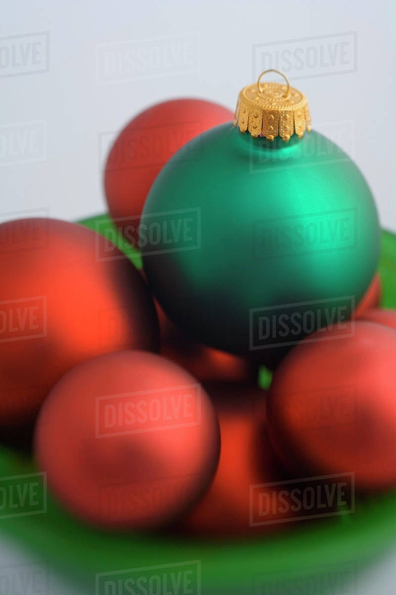 green and red christmas tree bulb ornaments piled in green glass bowl studio portrait