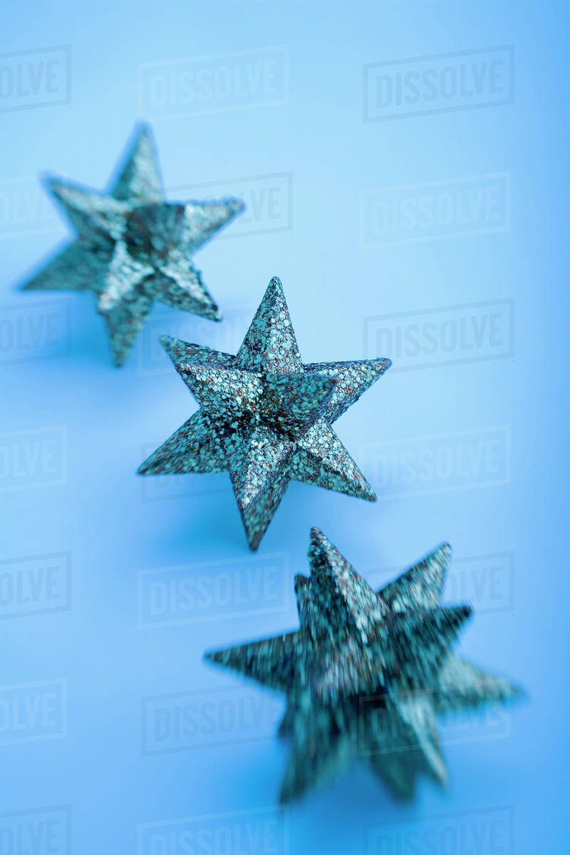 Three Gold Star Christmas Ornaments In Row Blurred On Edges With Blue Filter On White Background Studio Portrait Stock Photo