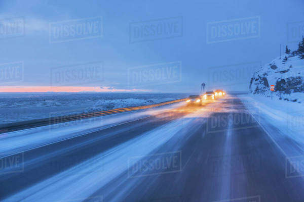 Traffic driving on the seward highway during a snowstorm at twilight in winter, beluga point;Anchorage, alaska, united states of america Royalty-free stock photo