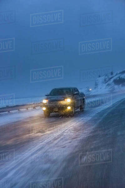 A truck driving on the seward highway during a snowstorm at twilight in winter, beluga point;Anchorage, alaska, united states of america Royalty-free stock photo