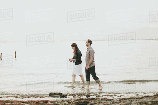 A Couple Walking Barefoot Along The Water's Edge; Crescent Beach, British Columbia, Canada Royalty-free stock photo