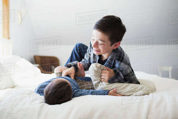 Brothers playing on a big bed at home; Victoria, British Columbia, Canada Royalty-free stock photo