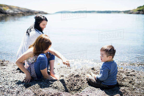A mother playing with her children at the water's edge; Victoria, British Columbia, Canada Royalty-free stock photo