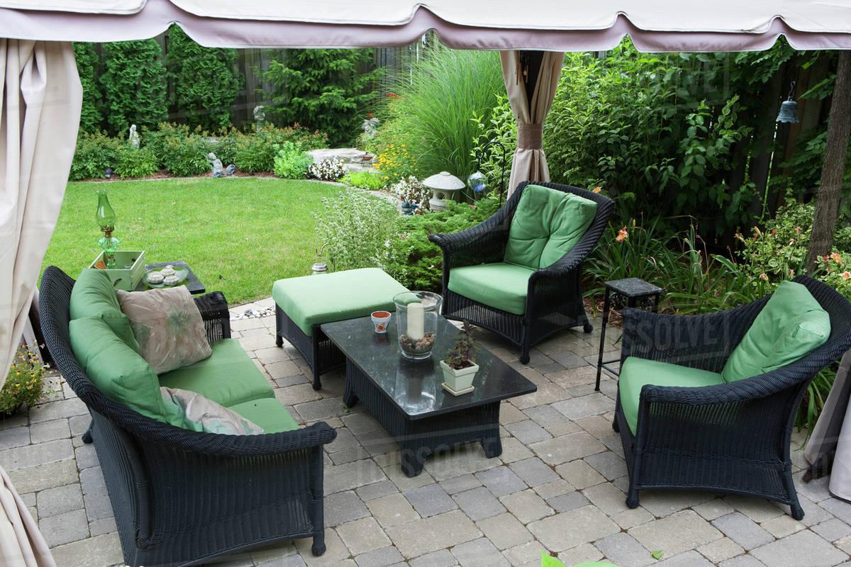 Covered patio furniture on stone patio in a backyard burlington ontario canada