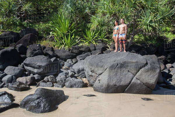 A couple stands on a large rock in their swimsuits;Green mount coolangatta gold coast queensland australia Royalty-free stock photo