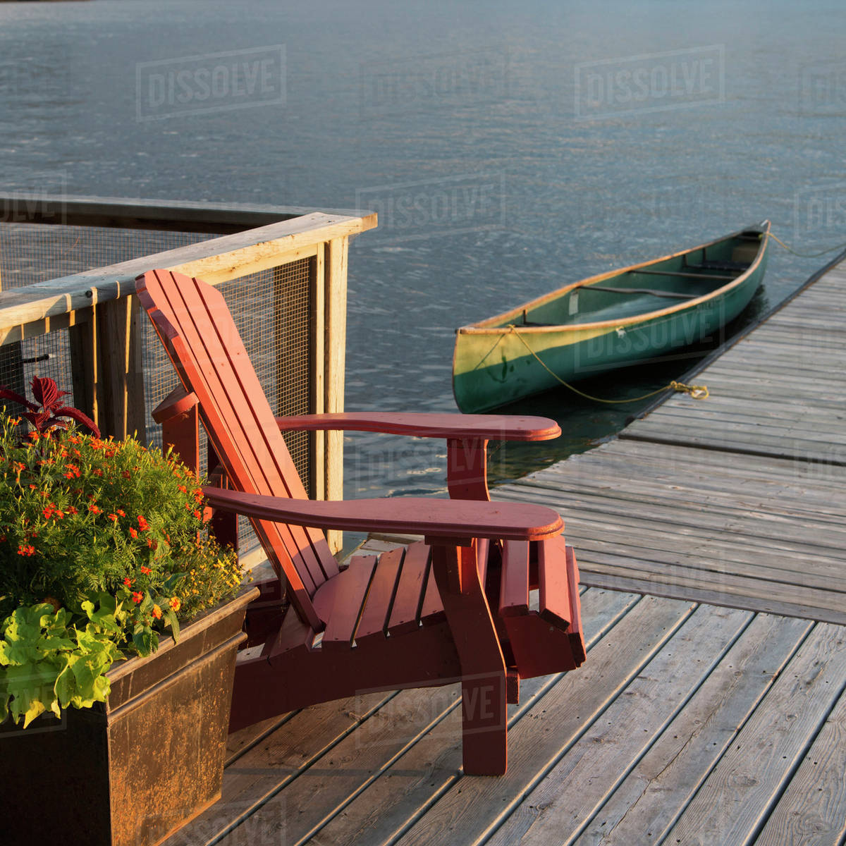 A canoe tied to a wooden dock with a chair and flower planter ... on wooden powerboat, wooden tube, wooden airboat, wooden cruiser, wooden yacht, wooden pontoon, wooden sloop, wooden speedboat, wooden barge, wooden warship, wooden motorboat, wooden sailboat, wooden cannon, wooden boat, wooden catamaran, wooden trawler, wooden pirogue, wooden ship, wooden houseboat, wooden rowing shell,