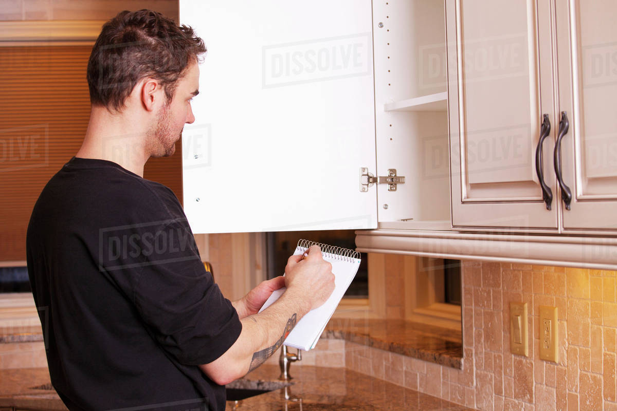Carpenter Measuring And Installing New Kitchen Cabinets ...