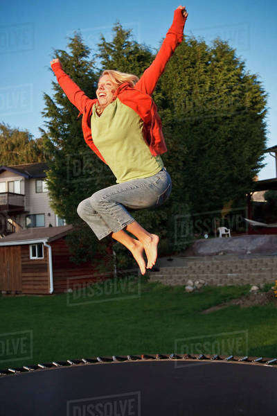 Woman Jumps On A Trampoline With Arms Raised; Ferndale, Washington, United States of America Royalty-free stock photo
