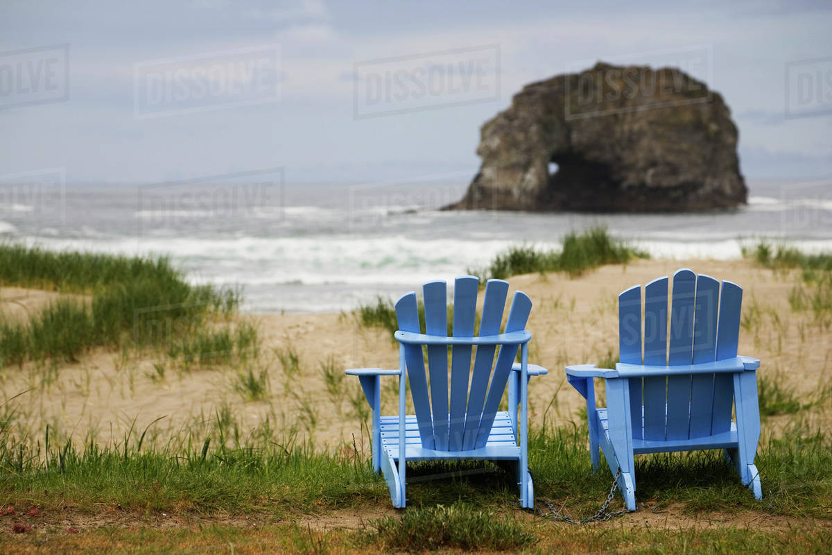 Two Blue Adirondack Chairs On A Grassy Beach With Rock Formations In The  Ocean; Rockaway Beach, Oregon, United States Of America