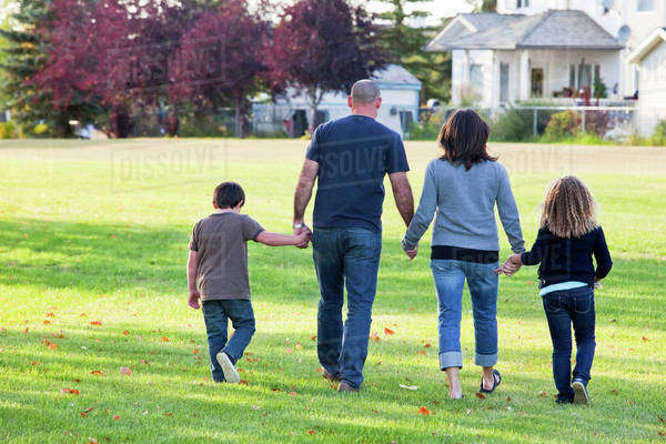 Family Walking Together In A Park; Beaumont, Alberta, Canada Royalty-free stock photo