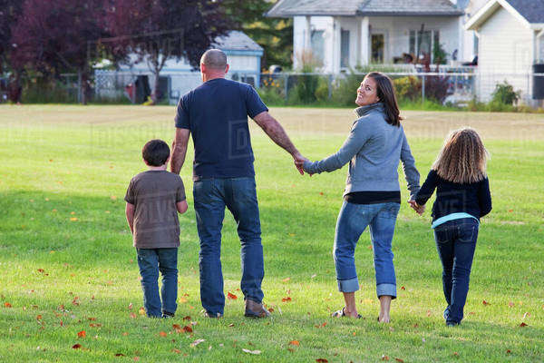 Family Walking Together In A Park And Mother Smiling; Beaumont, Alberta, Canada Royalty-free stock photo