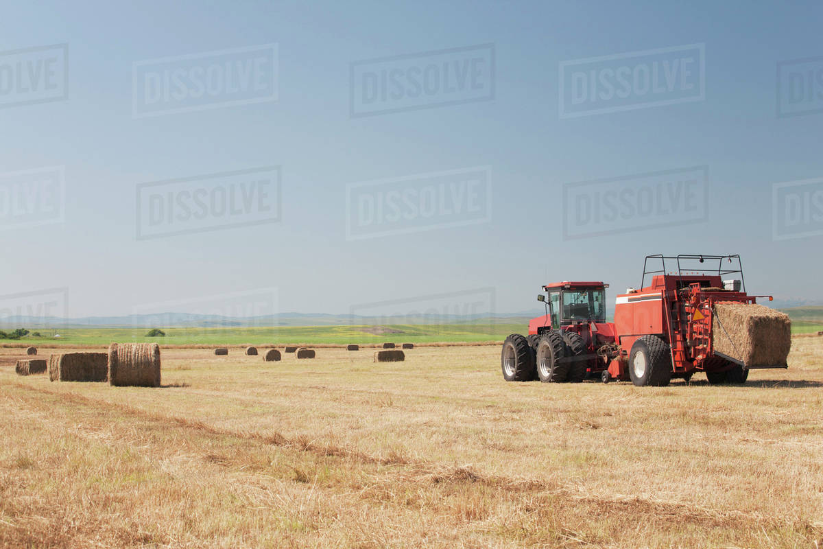 Hay Baler In A Field With Blue Sky
