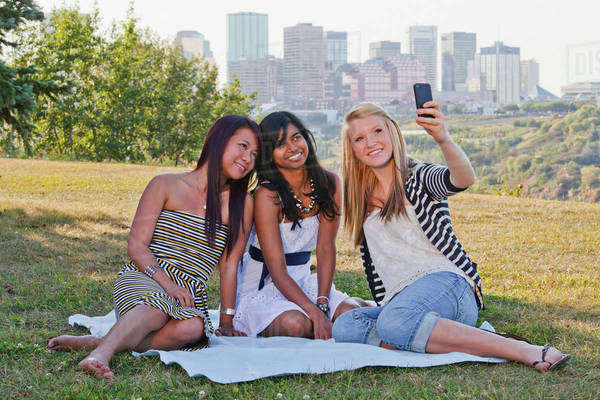 Friends Taking A Picture In A City Park With The City Skyline In The Background; Edmonton, Alberta, Canada Royalty-free stock photo