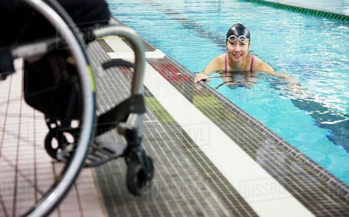 A Paraplegic Woman Swims In A Pool With Her Wheelchair At The ...