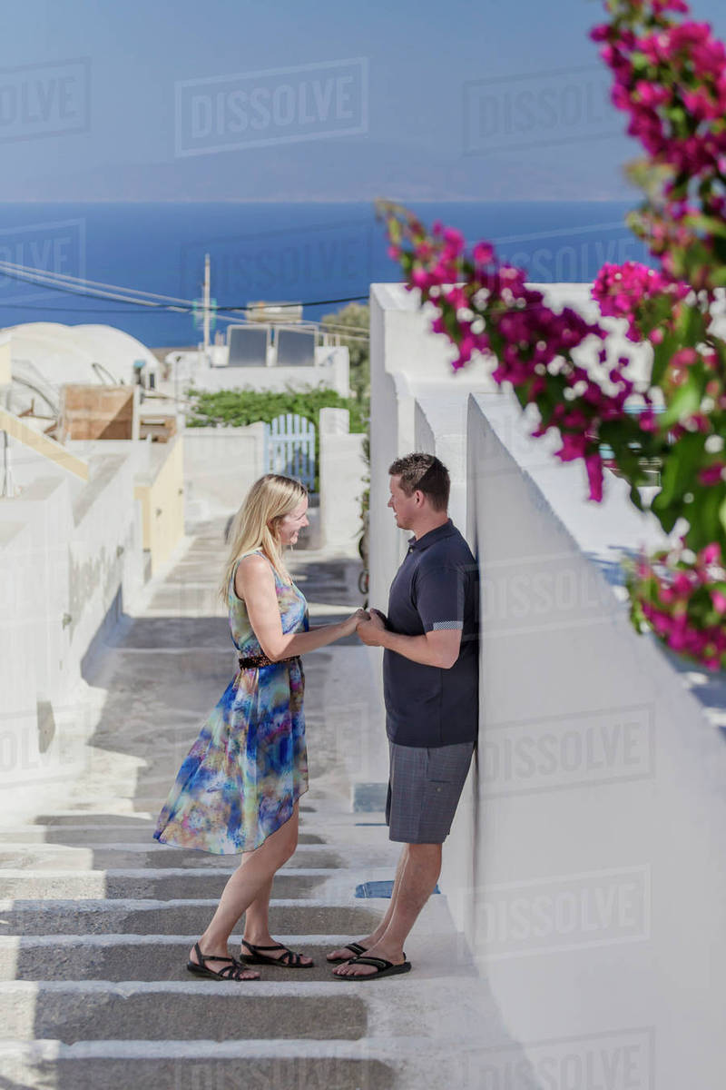 A Couple Stands On A Walkway By A Whitewash Wall On A Greek Island