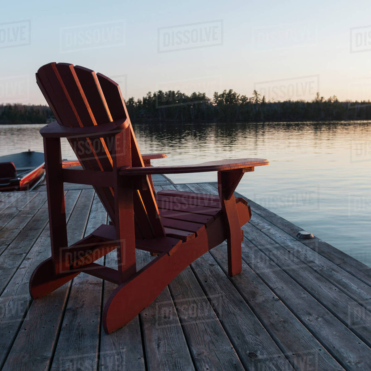 A Red Adirondack Chair Sitting On A Wooden Dock On A Lake At Sunset; Lake  Of The Woods, Ontario, Canada