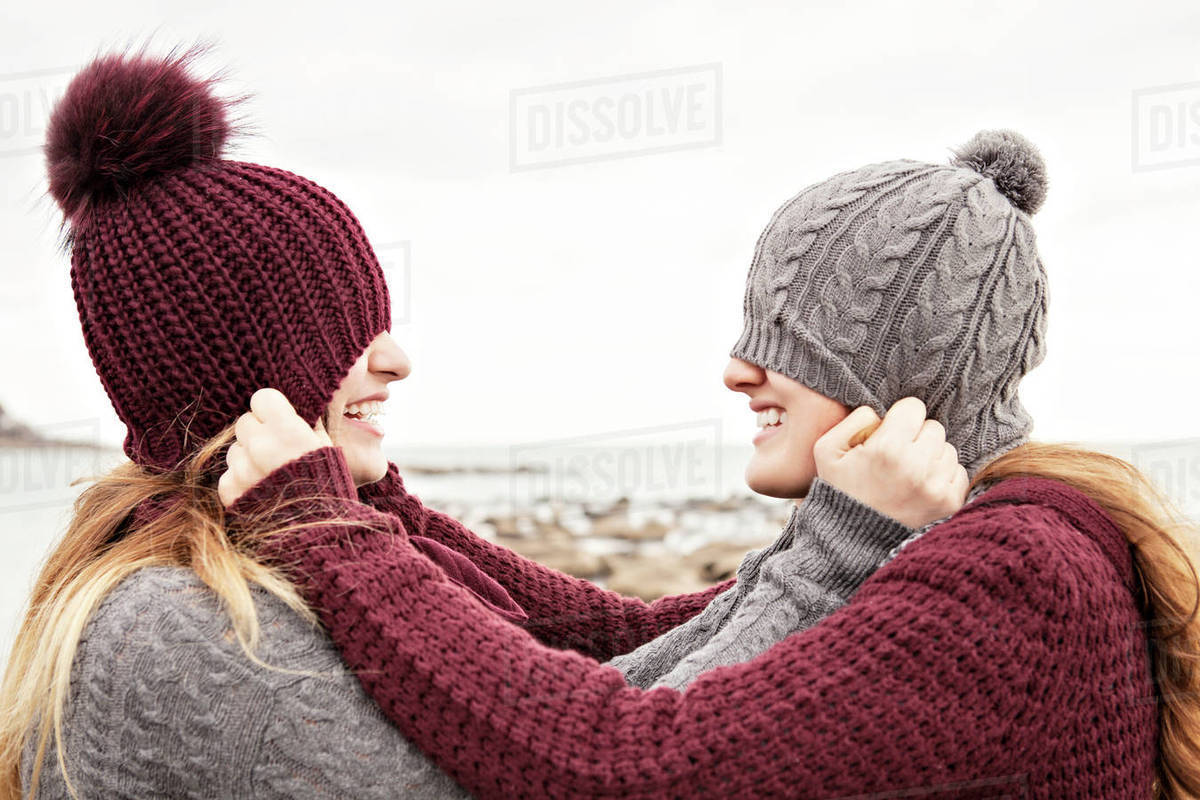 363129d0e21 Two friends playing on the beach wearing knit hats and scarves, Woodbine  Beach; Toronto, Ontario, Canada stock photo