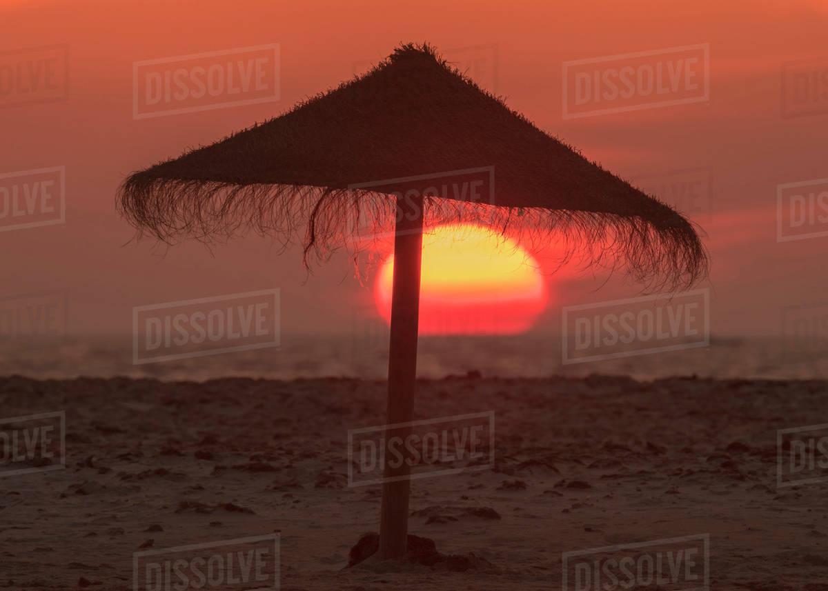 3cbf29e8b9 Silhouette of a beach umbrella on the beach with a colourful sun sinking  into the horizon over the ocean; Tarifa, Cadiz, Andalusia, Spain stock photo