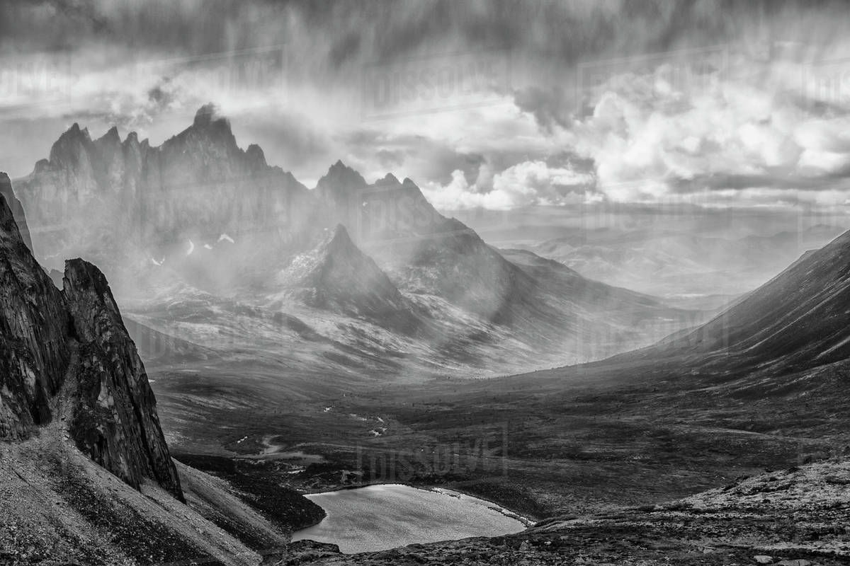 Black and white image of a rain storm over the tombstone valley in tombstone territorial park with tombstone mountain shrouded in the rain in the