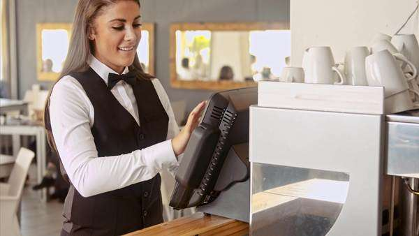 Wide shot of manager swiping touch payment terminal as waitress picking up table bill to service customer in restaurant or cafe Royalty-free stock video