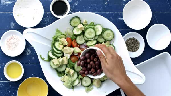 Woman's hands preparing and making a Greek salad recipe. Royalty-free stock video