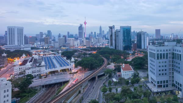 Timelapse of a beautiful sunrise of Kuala Lumpur city view from rooftop of a building with moving vehicle, clouds and sunlight burst. Panning right Royalty-free stock video
