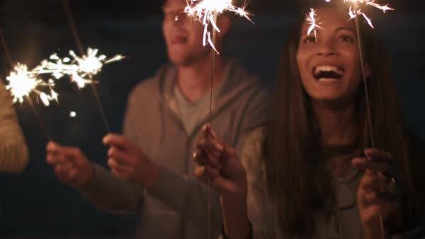 Friends light sparklers on beach party for celebration laughing and smiling together Royalty-free stock video